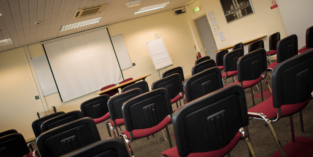 Meeting rooms for Barnsley office space tenants, room full of chairs with whiteboard and pulldown for projector